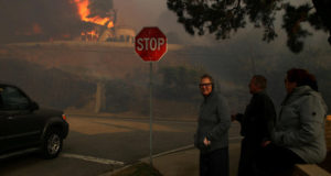 FILE PHOTO: Neighbors watch as a house burns during a wind driven wildfire in Ventura California